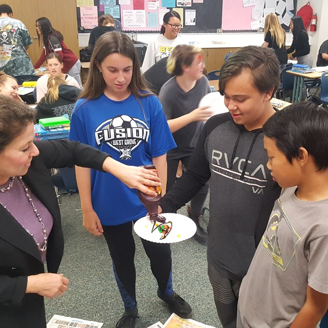 Students participate in a scientific experiment with delectable cake.